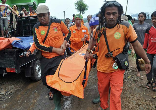 Rescue workers carry the body of a landslide victim at Pasuruhan village in Wonosobo December 12, 2014
