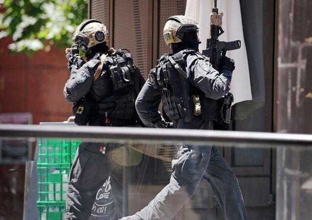 A police officer runs across Martin Place near Lindt cafe, where hostages are being held, in central Sydney December 15, 2014