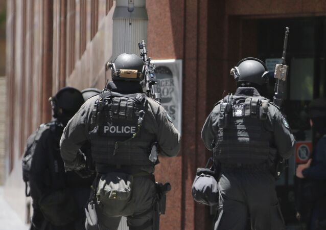 Armed police stand at the ready close to a cafe under siege at Martin Place in the central business district of Sydney, Australia, Monday, Dec. 15, 2014
