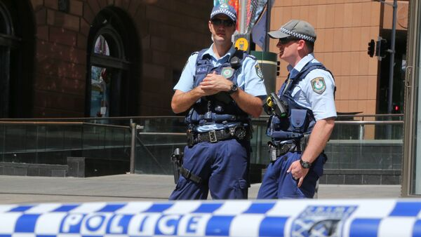 Police stand near a police line to stop pedestrian access close to a cafe under siege at Martin Place in Sydney, Australia, Monday, Dec. 15, 2014 - Sputnik International