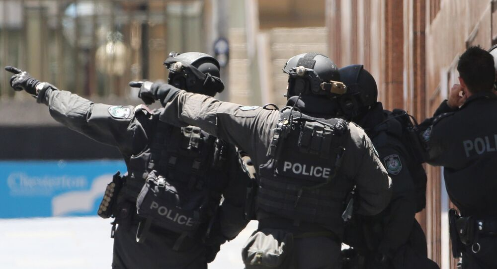 Armed police officers point as they stand at the ready close to a cafe under siege at Martin Place in Sydney, Australia, Monday, Dec. 15, 2014
