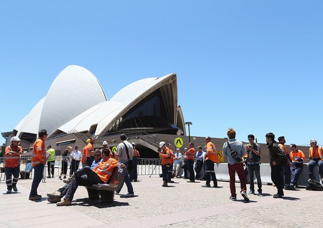 Construction workers gather in front of the Sydney Opera House after being evacuated