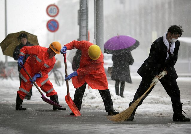 Railway station workers shove snow from the street in Yokohama, Japan, Saturday.