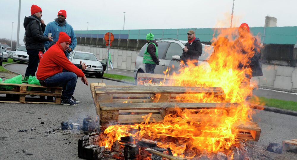 Workers and members of trade unions block a road leading to a Brussels airport