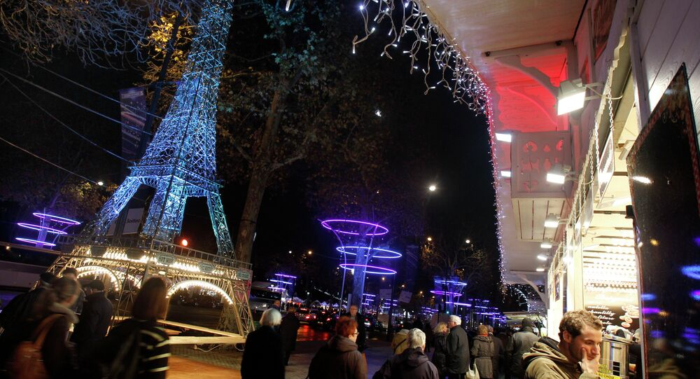 Tourists and Parisians wander on the Champs Elysees with the Christmas market set up for the Christmas period, in Paris