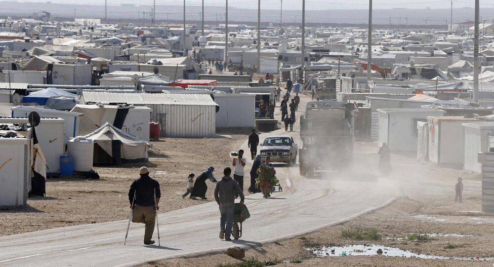 Syrian refugees walk at the Al Zaatari refugee camp in the Jordanian city of Mafraq, near the border with Syria, December 7, 2014
