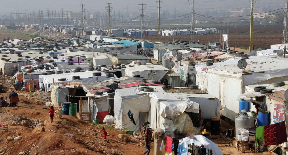 Syrian refugees walk at a refugee camp in Zahle in the Bekaa valley November 18, 2014