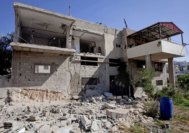 Palestinian inspect the home of Palestinian Ziad Awad in the town of Idna,13 kilometers (8 miles) west of the West Bank city of Hebron, Wednesday, July 2, 2014