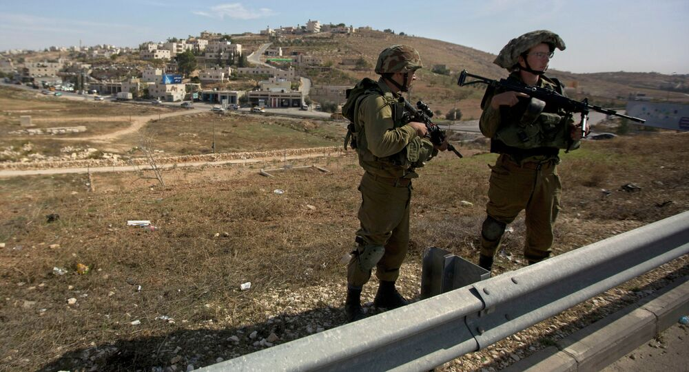 Israeli soldiers stand guard on the main road near the West bank village of Bet Sahour during the funeral of Dalia Lemkus, at the West Bank Jewish settlement of Tekoa, Tuesday, Nov. 11, 2014