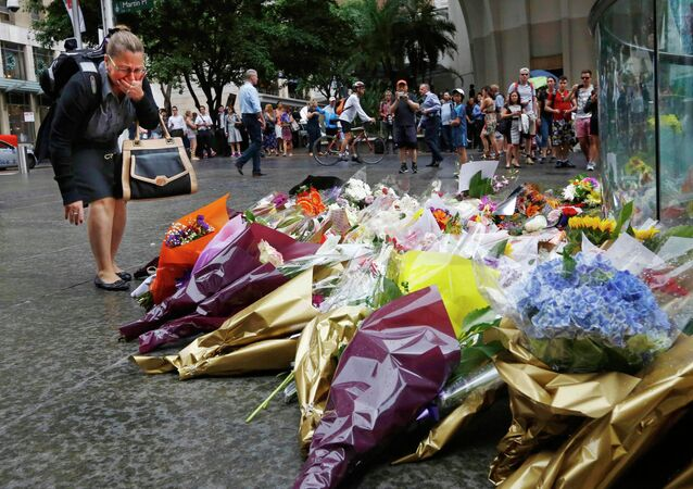 A woman reacts after placing a floral tribute for those who died in the Sydney cafe siege, near the site of the incident, in Martin Place December 16, 2014