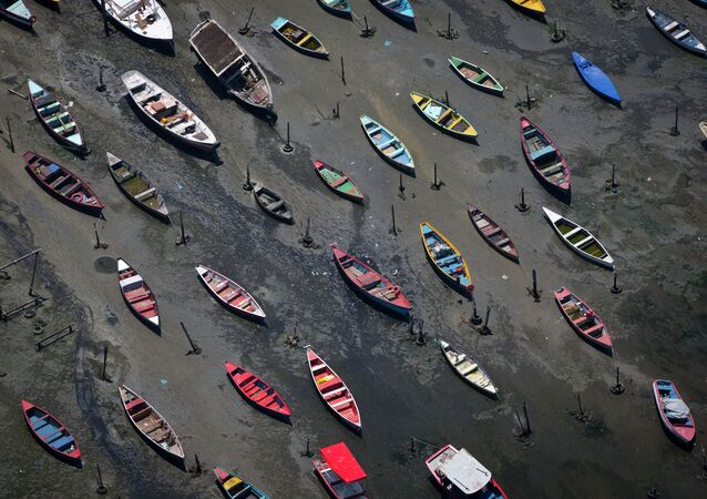 In this Nov. 19, 2013 file photo, small boats sit on the polluted shore of Guanabara Bay in the suburb of Sao Goncalo, across the bay from Rio de Janeiro, Brazil