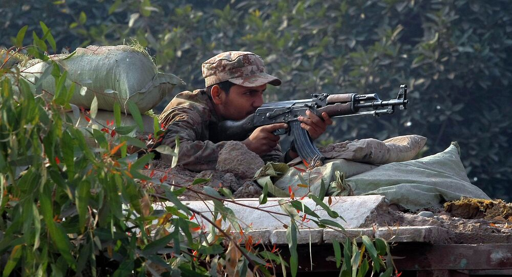 A Pakistani army soldier takes position on a bunker close to a school under attack by Taliban gunmen in Peshawar, Pakistan, Tuesday, Dec. 16, 2014