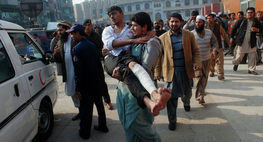 A man carries a student, who was injured during an attack by Taliban gunmen on the Army Public School, after he received treatment at a hospital in Peshawar, December 16, 2014