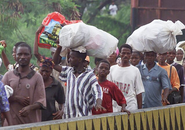People carry food stuffsand other belongings across the New Bridge in Monrovia, Liberia