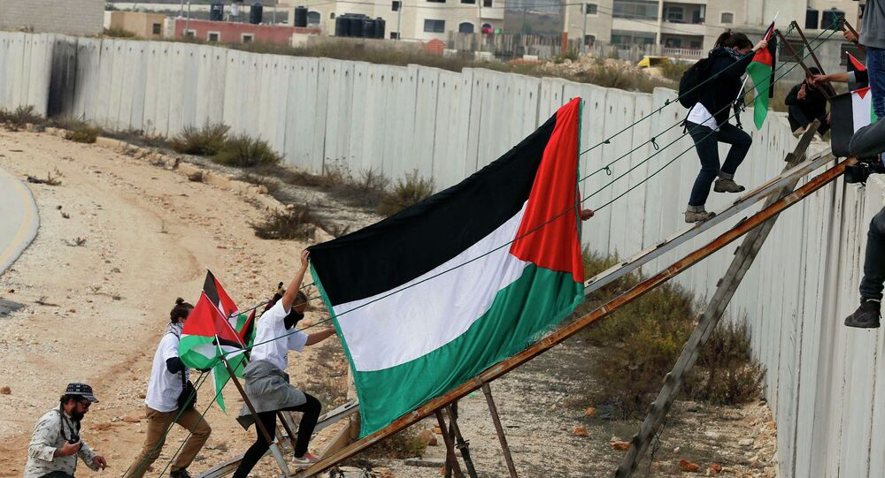 Foreign activists and Palestinian protesters use a metal ramp to cross over a section of the controversial Israeli barrier during a protest over tension in Jerusalem, near the Israeli Qalandia checkpoint between the West Bank city of Ramallah and Jerusalem