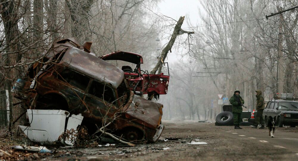 Independent supporters stand guard next to cars damaged during fighting between  independent supporters and Ukrainian government forces near Donetsk Sergey Prokofiev International Airport, eastern Ukraine, December 16, 2014.