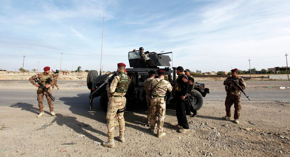 Members of the Iraqi security forces carry their weapons during an intensive security deployment on the outskirts of Baiji, north of Baghdad, December 8, 2014.