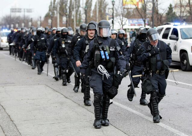 Police wearing riot gear walk past Edward Jones Dome following an NFL football game between the St. Louis Rams and the Oakland Raiders