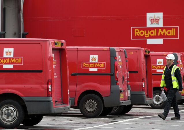 A post office worker walks by Royal Mail vans, at the London's latest sorting office Mount Pleasant