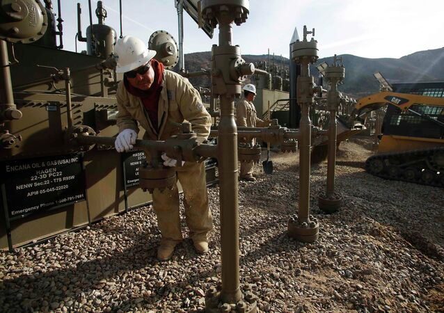 Workers put the final touches on a natural gas well platform owned by Encana south of Parachute, Colorado