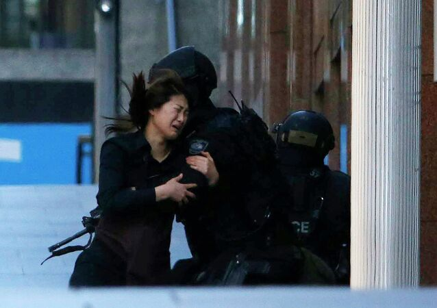 A hostage runs towards a police officer outside Lindt cafe, where other hostages are being held, in Martin Place in central Sydney