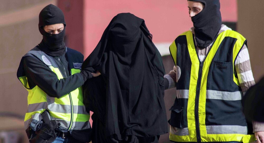 Masked Spanish police officers lead a detained woman in Melilla