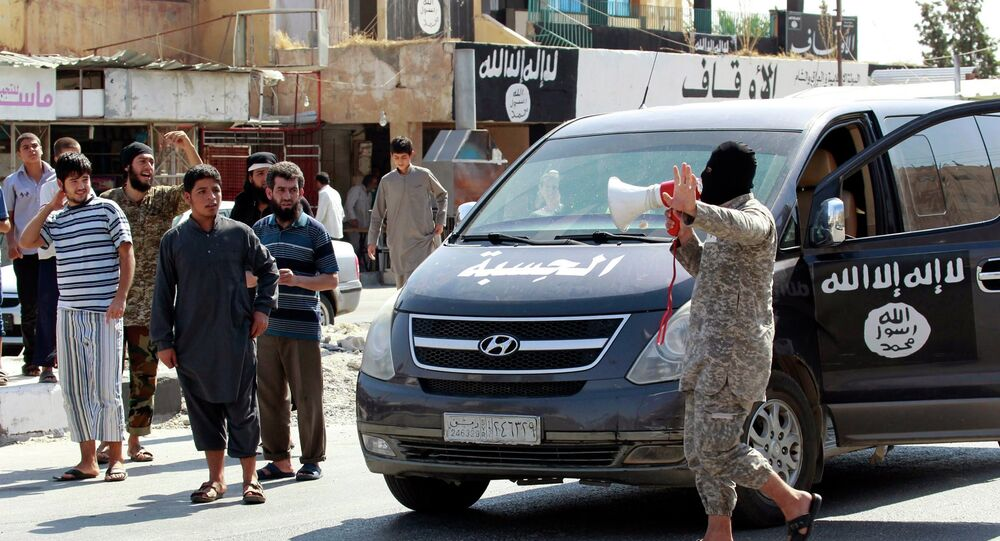 An Islamic State militant uses a loud-hailer to announce to residents of Taqba city that Tabqa air base has fallen to Islamic State militants, in nearby Raqqa city August 24, 2014.