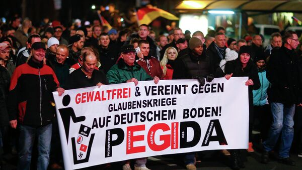Participants hold a banner during a demonstration called by anti-immigration group PEGIDA, a German abbreviation for Patriotic Europeans against the Islamization of the West, in Dresden December 15, 2014. Several thousands opponents of Germany's policy towards asylum seekers and Islam took part in the protest in the eastern German town on Monday. The banner reads, Peaceful and united against wars of religion in Germany! - Sputnik International