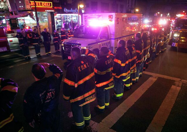 An ambulance carrying one of the two New York Police officers who were shot dead passes by a New York Fire Department honor guard along Broadway in the Brooklyn borough of New York, December 20, 2014.