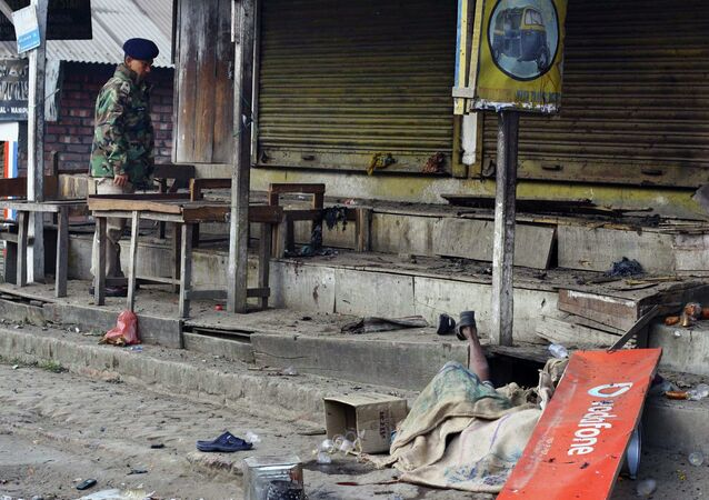 The body of a blast victim is seen as an Indian policeman stands at the site of an explosion in Imphal, the capital of Manipur state, India, Sunday, Dec. 21, 2014