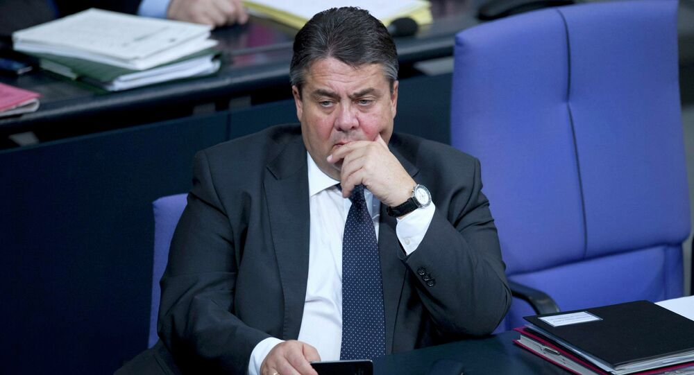 Germany's Economy Minister Sigmar Gabriel holds a MOBILE phone during a debate at the lower house of parliament Bundestag in Berlin, November 26, 2014