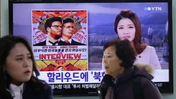 People walk past a TV screen showing a poster of Sony Picture's The Interview in a news report, at the Seoul Railway Station in Seoul, South Korea, Monday, Dec. 22, 2014 - Sputnik International