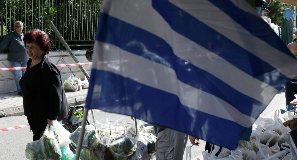 People holding shopping bags full of fruits and vegetables pass a Greek flag during a protest by farmers' market vendors in the northern Athens' suburb of Gerakas on Monday, May 5, 2014