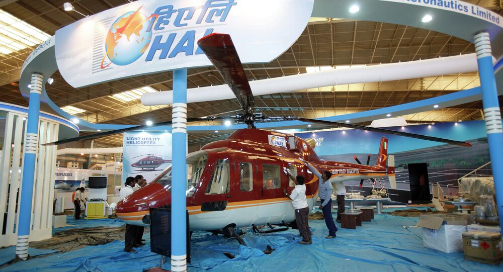 Workers polish a helicopter at the stall of Hindustan Aeronautics Ltd. on the eve of Aero India 2011 at Yelahanka air base on the outskirts of Bangalore, India, Tuesday, Feb. 8, 2011