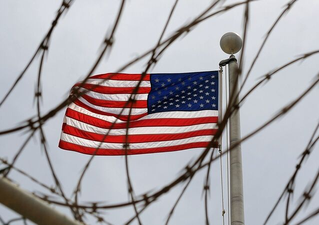 An American Flag is seen through razor wire at Camp VI in Camp Delta where detainees are housed at Naval Station Guantanamo Bay in Cuba