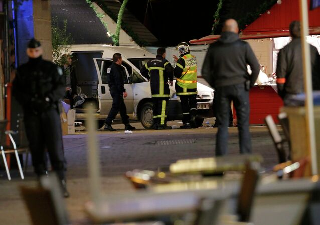French police and firemen work near a van