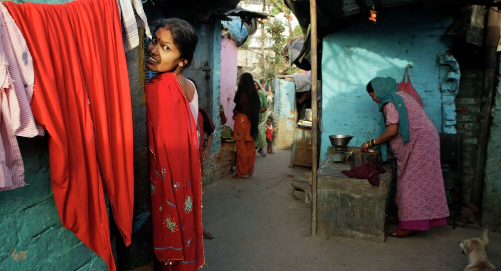 An Indian woman reacts to the camera as another sells meat in a narrow alley at a slum area in New Delhi, India, Tuesday, May 21, 2013