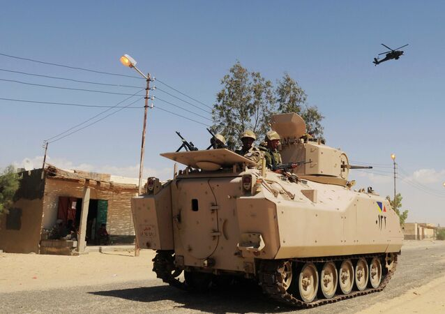 In this Tuesday, May 12, 2013 file photo, Egyptian Army soldiers patrol in an armored vehicle backed by a helicopter gunship during a sweep through villages in in Sheikh Zuweyid, northern Sinai, Egypt