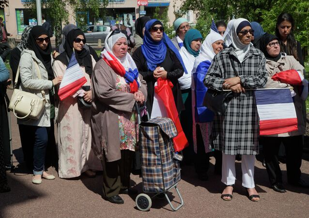 Woman wearing traditional muslim scarf and holding French flags gather outside the town hall in Mantes la Ville, north west of Paris, Friday, May 16, 2014, in protest of the ban of a new mosque