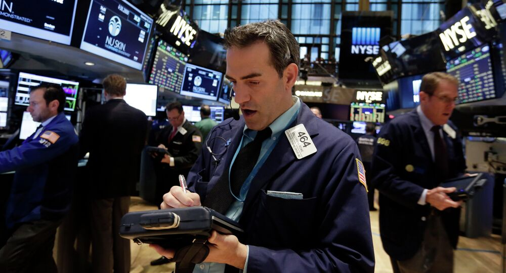 Trader Gregory Rowe, center, works on the floor of the New York Stock Exchange, Tuesday, Nov. 18, 2014