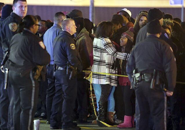 Police hold back a crowd at the perimeter of a scene on Wednesday, Dec. 24, 2014, following a shooting Tuesday at a gas station in Berkeley, Mo. St. Louis