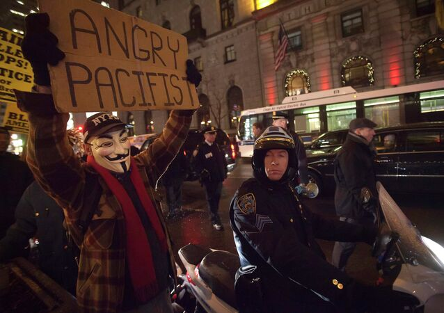 A demonstrator wearing a Guy Fawkes mask walks up 6th Ave as he protests against the police in the Manhattan borough of New York December 23, 2014