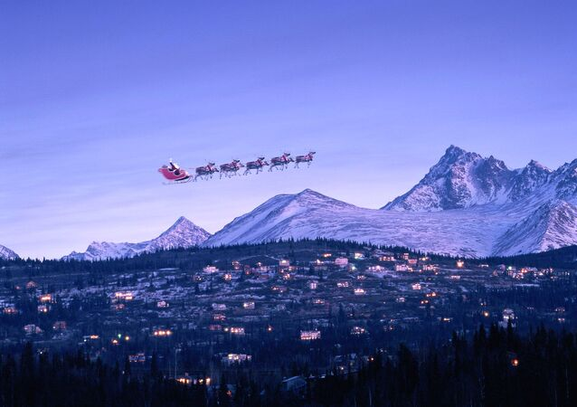 Santa in sleigh & reindeer fly over houses