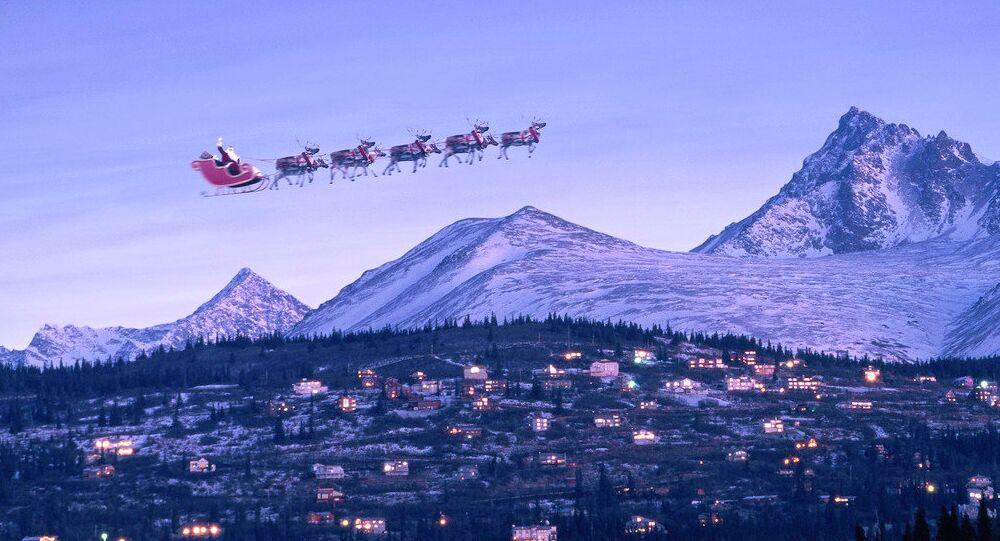 Santa in sleigh & reindeer fly over houses