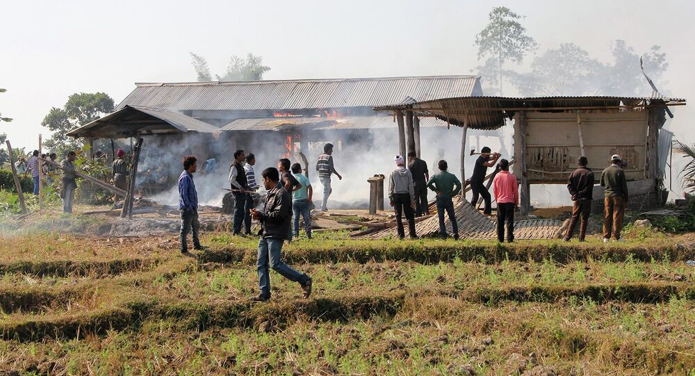 Tribal plantation workers burn houses belonging to indigenous Bodo tribesmen after ethnic clashes in Balijuri village, in Sonitpur district in the northeastern Indian state of Assam