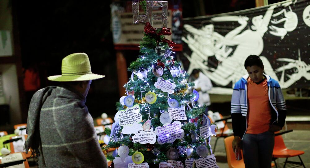 Men look at a Christmas tree, with pictures of the 43 missing trainee teachers, in the Ayotzinapa Teacher Training Raul Isidro Burgos College in Ayotzinapa, on the outskirts of Chilpancingo, Guerrero