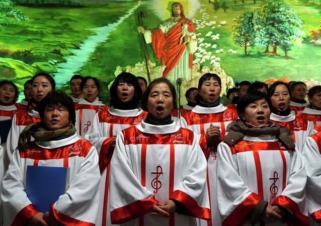 Choristers sing Christmas carols in front of a figure of Jesus Christ, during a mass at a catholic church in Shenyang, Liaoning province