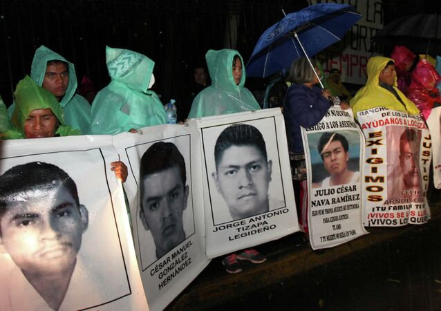 The relatives of 43 missing college students hold posters with images of their missing loved ones