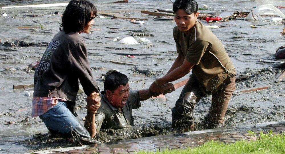 Acehnese youths try to pull a man to higher ground through a flooded street a moment after tsunami strike in the provincial capital of Banda Aceh, Aceh province, Indonesia