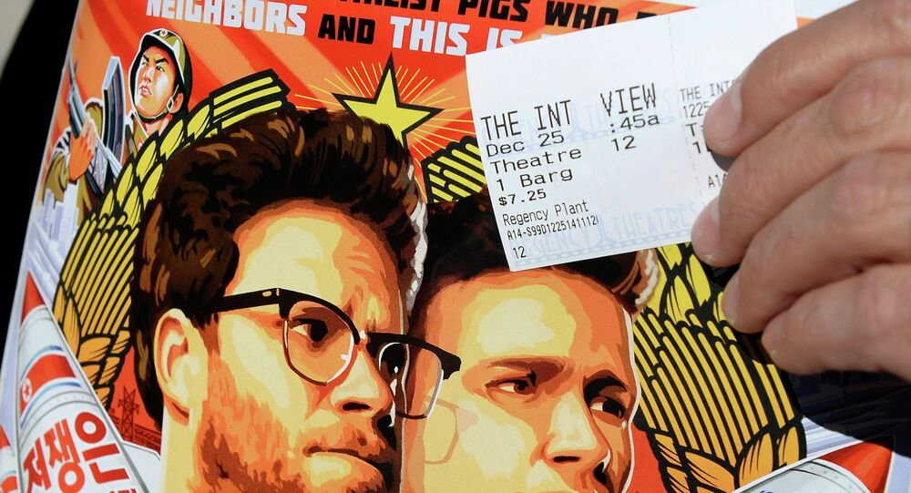Dennis Lavalle holds a ticket and a poster of the film The Interview